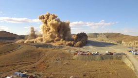 Aerial view A massive explosion rocks in desert. Dirt and metal shards into the air stock footage