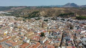 Aerial view of medieval Moorish castle of Alcazaba of Antequera on background with cityscape on sunny fall day, Malaga