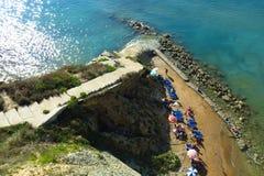 Aerial view Mediterranean beach sunbathers Corfu Greece. Sunbathers relax on a sandy beach beside the turquoise blue Mediterranean Sea on the island of Corfu Stock Photography