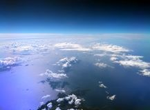 Aerial view of the Mediterranean sea taken from an airplane with dark blue sky and clouds reflected on the water and an island. In the bottom of the image Royalty Free Stock Photo