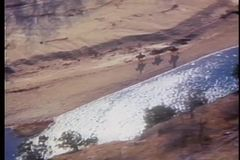 Aerial view of men on horses galloping alongside Buffalo River in Arkansas stock footage