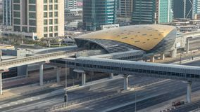 Aerial view of Metro station near Jumeirah lakes towers skyscrapers timelapse with traffic on sheikh zayed road. Bus station near exit. Sunset time with long stock footage