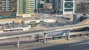 Aerial view of Metro station near Jumeirah lakes towers skyscrapers timelapse with traffic on sheikh zayed road. Bus station near exit. Sunset time with long stock video footage