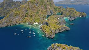 Aerial view of Miniloc Island. El-Nido, Palawan. Philippines. Limestone karst rock ridge formation surrounded by ocean. And plenty tourist boats on tour A stock footage