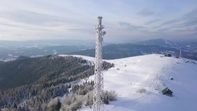 Flight over the mobile tower on top of Carpathian mountains covered with snow. Clear frosty weather. Aerial view on mobile tower on the top of Carpathian stock footage