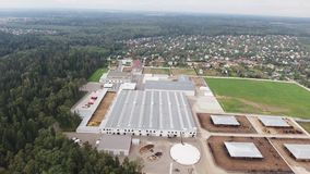 Aerial view of modern clean fenced animal farm with paddocks for cows and sheeps. Aerial view of several roofs of buildings belonged to modern, clean, grey stock video footage