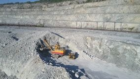 Aerial view excavator digs grey ground hill in asbestos pit. Aerial view modern powerful excavator digs large grey ground hill in huge asbestos pit in sunny stock video
