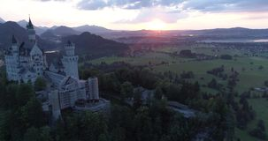 Aerial view of morning sunset of the Neuschwanstein castle in Bavarian Alps, Bavaria, Germany in 4K. Ready for Color. Amazing aerial sunset view of the stock video footage