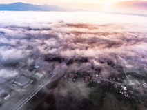 Aerial view of morning town covered by mist, sunrise Stock Image
