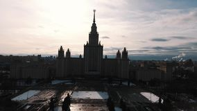 Aerial view of Moscow State University building silhouette, snow covered park stock footage