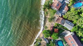 Aerial view in motion of houses with swing pool near the beach in Sri Lanka. Houses with a swimming pool are located near the sandy beach washed by sea waves at stock video