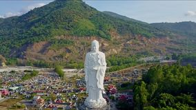 Aerial View Motion from Right to Left of Buddha Statue. Aerial view motion from right to left of giant white buddha statue against fields and green mountains stock video footage