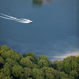 Aerial View : motorboat waterskiing on a lake. Forming a nice curve wake Stock Photo