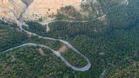 Aerial view of mountain curve road. Green forest at sunset in summer in Europe. Landscape with asphalt road, trees on the rocks. stock photos