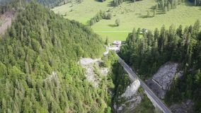 Chalet in alps. Aerial view mountain and forest landscape of alps with chalet and road stock footage