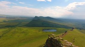 Aerial view of the mountain range Sunduki, green fields sky before the storm in the Republic of Khakassia. Russia.  stock footage