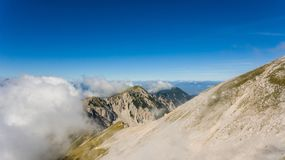 Aerial view of mountain ridge surrounded with clouds. Stol in Karavanke, Slovenia Royalty Free Stock Images