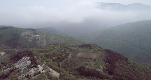 Aerial view with mountain road and heavy mist at the background. Cinema 4k forward fly stock video