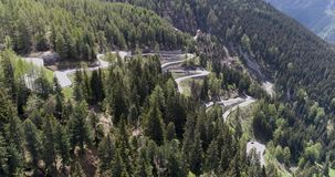 Aerial view of mountain serpentine road with trucks and cars driving on zig zag go up and down in Europe Switzerland 4K. Aerial view of mountain serpentine road stock video