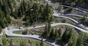 Aerial view of mountain serpentine road with trucks and cars driving on zig zag go up and down in Europe Switzerland 4K. Aerial view of mountain serpentine road stock video footage