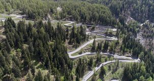 Aerial view of mountain serpentine road with trucks and cars driving on zig zag go up and down in Europe Switzerland 4K stock video footage