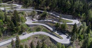 Aerial view of mountain serpentine road with trucks and cars driving on zig zag go up and down in Europe Switzerland 4K. Aerial view of mountain serpentine road stock footage