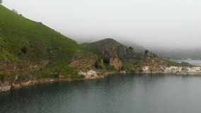 Aerial view mountain turquoise lake among the hills in cloudy day weather and fog. Landscapes of the North Caucasus.  stock footage