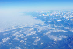 Aerial view on mountains. Aerial view on snowy mountains and blue clear sky Royalty Free Stock Photo