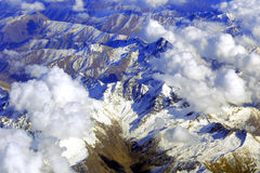 Aerial view of mountains from airplane, clouds Royalty Free Stock Image