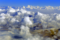 Aerial view of mountains from airplane, clouds, sky Royalty Free Stock Photo
