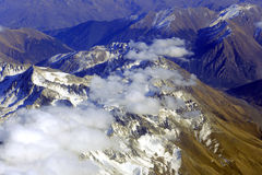 Aerial view of mountains from airplane, clouds Stock Images
