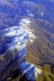 Aerial view of mountains from airplane, clouds, sky Stock Image