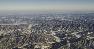 Aerial view of mountains and clouds on top. See the magnificent snow capped mountains in the plane royalty free stock photo