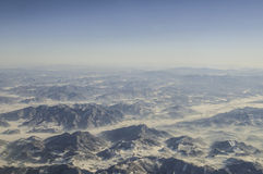 Aerial view of mountains and clouds on top. See the magnificent snow capped mountains in the plane stock photos