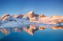 Aerial view at the mountains and reflection on the water surface. Lofoten islands, Norway. Natural landscape during sunrise from air. Drone landscape stock photography