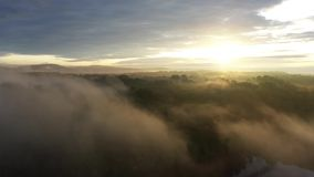 Aerial view moving above a foggy sunrise stock video footage