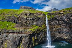 Aerial view of Mulafossur waterfall in Gasadalur village in Faroe Islands, North Atlantic Ocean. Photo made by drone from above.