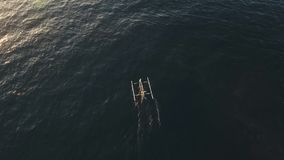 Fishing boats on the sea. Aerial view national Balinese fishing boat with fishermen sails to the sea. Aerial footage stock video