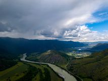 Aerial view of the nature of the Altai Mountains during an approaching thunderstorm with clouds and, as yet, a bright shining on royalty free stock photography