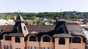 Aerial view of the new brown tiled roof with a weather vane. Forest in the background royalty free stock image