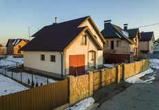 Aerial view of new residential house cottage and attached garage with shingle roof on fenced yard on sunny winter day in modern. Suburban area. Perfect royalty free stock photography