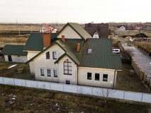 Aerial view of new residential house cottage and garage or barn with shingle roof on fenced yard on sunny day.  stock image