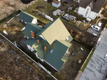 Aerial view of new residential house cottage and garage or barn with shingle roof on fenced yard on sunny day.  royalty free stock photography