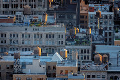 Aerial view of New York rooftops and water towers. Late afternoon light over Chelsea building rooftops illuminating NYC typical water towers. Urban view of Stock Photos
