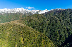 Aerial view of New Zealand mountains, wilderness landscape. Aerial view of New Zealand mountains. View from above on snow caped mountains with green forest over stock image