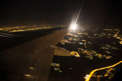 Aerial view of night city landscape. Earth viewed from airplane. Under aircraft wing. Lights of modern city from the bird fly Royalty Free Stock Images