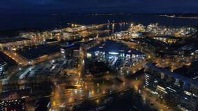 Aerial view of the night city with street lighting and moving traffic near the sea and ships in the port.  stock video footage