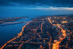 Aerial view of night city Voronezh with illuminated roads, buildings, river and bridge, drone shot.  stock photography