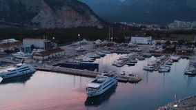 Aerial view on night yacht parking. Stock. Landscape with boats in marina bay, sea, city, mountains.Top view from drone. Aerial view on night yacht parking stock video footage