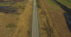 Aerial view of non-urban landscape, road and fields in 4K.  stock video footage